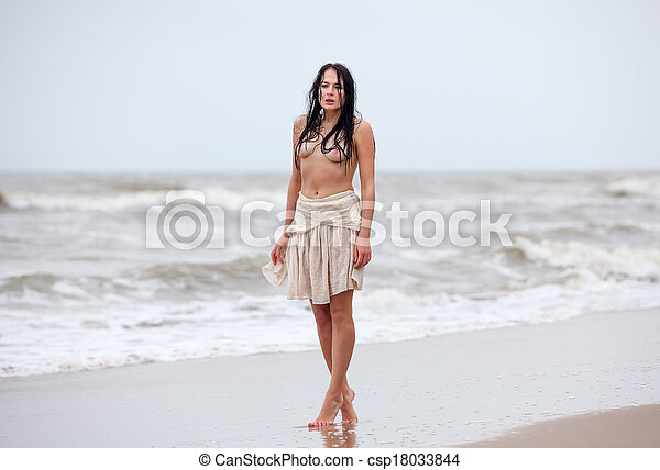 seminude woman in the cold sea waves - csp18033844