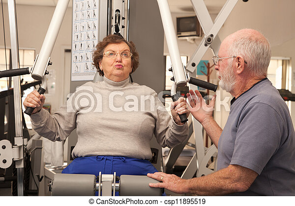 Senior Adult Couple Working Out Together in the Gym - csp11895519