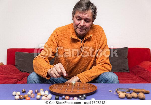 senior adult plays peg Solitaire - csp17607212
