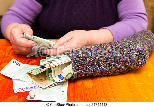 Senior adult with a sock full of money - csp24744443