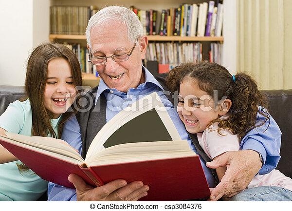 senior and children reading - csp3084376