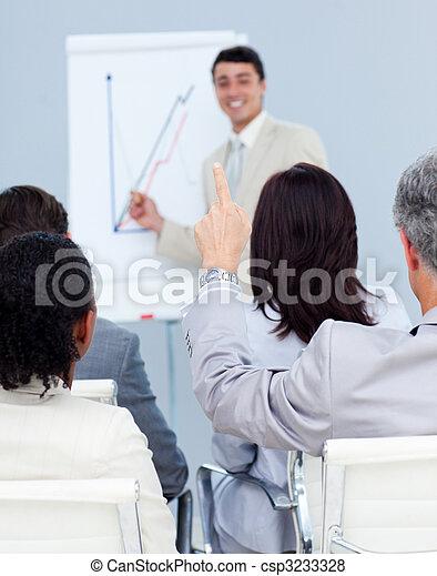 Senior businessman asking a question at a presentation - csp3233328
