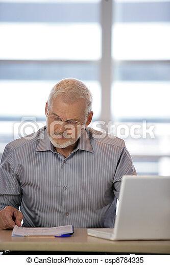 Senior businessman at his desk - csp8784335