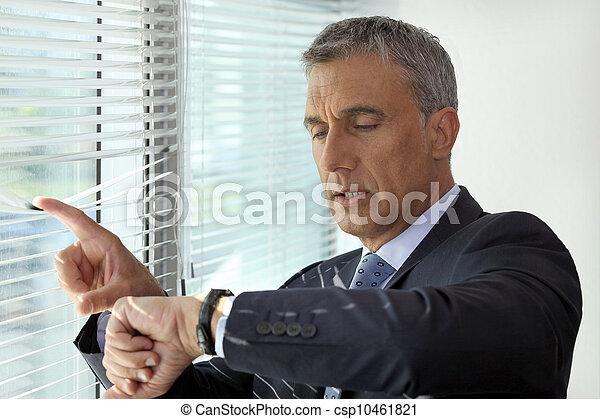 Senior businessman checking the time - csp10461821