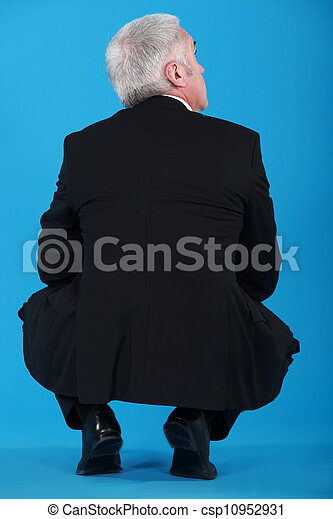 Senior businessman crouching with back to camera - csp10952931