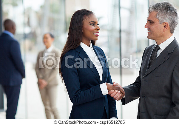 senior businessman handshaking with young businesswoman - csp16512785