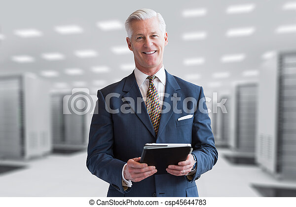 Senior businessman in server room - csp45644783