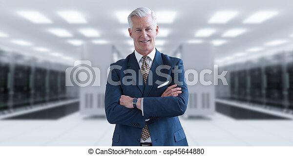 Senior businessman in server room - csp45644880