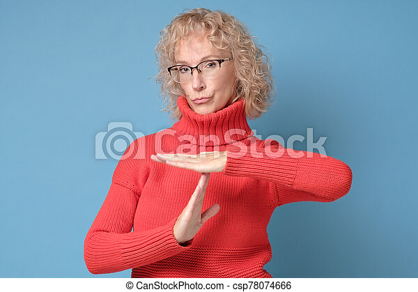 Senior caucasian woman in red sweater and glasses making time out gesture - csp78074666