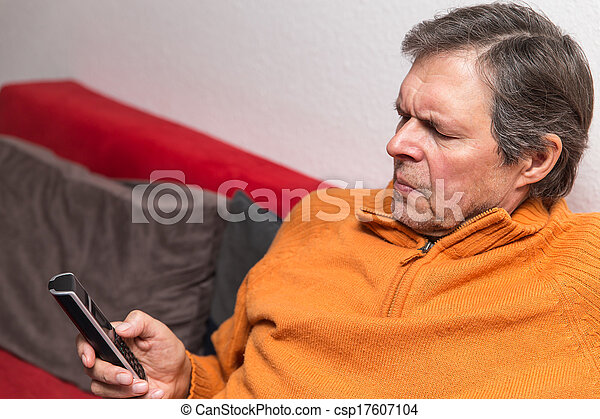 senior citizen on a couch with phone - csp17607104