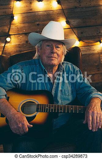 b3baf0e577ec5 Senior country and western musician sitting with guitar.