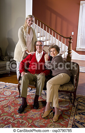 Senior couple at home on sofa with adult daughter - csp3790785