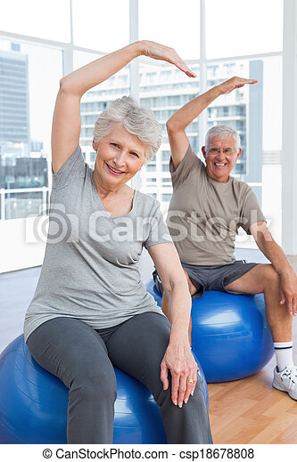 Senior couple doing stretching exercises on fitness balls - csp18678808