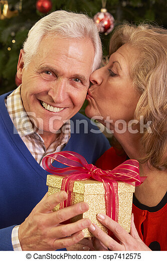 Senior Couple Exchanging Christmas Gifts - csp7412575