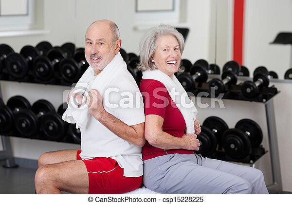 Senior couple exercising at a gym - csp15228225