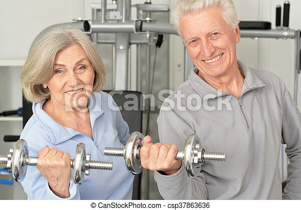 senior couple exercising in gym - csp37863636