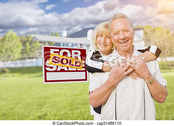 Senior Couple in Front of Sold Real Estate Sign and House - csp31486110