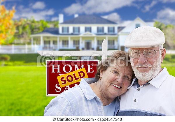 Senior Couple in Front of Sold Real Estate Sign and House - csp24517340