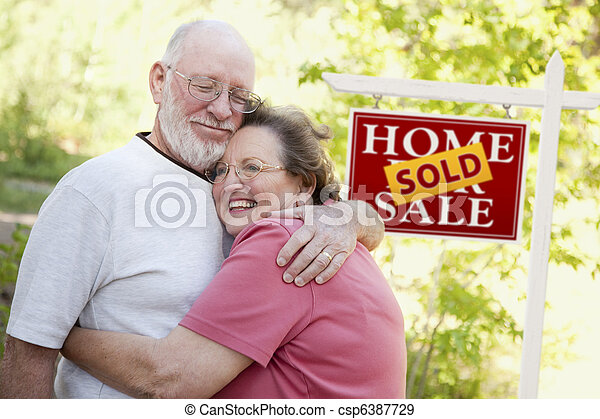 Senior Couple in Front of Sold Real Estate Sign - csp6387729