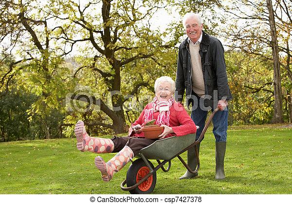 Senior Couple Man Giving Woman Ride In Wheelbarrow - csp7427378