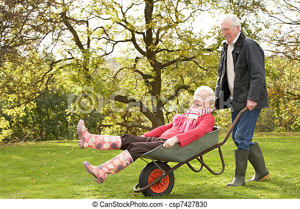 Senior Couple Man Giving Woman Ride In Wheelbarrow - csp7427830