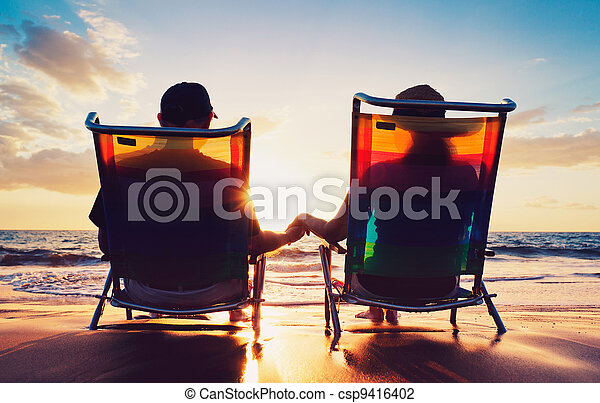 senior couple of old man and woman sitting on the beach watching sunset - csp9416402
