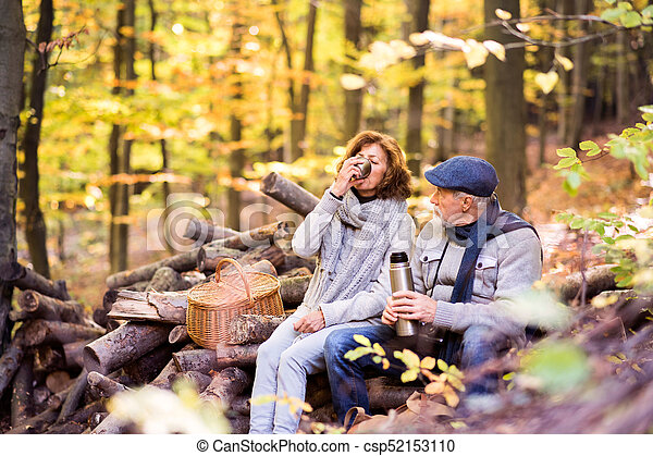 Senior couple on a walk in autumn forest. - csp52153110