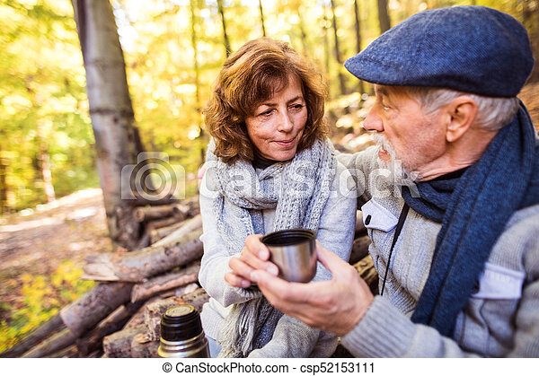 Senior couple on a walk in autumn forest. - csp52153111