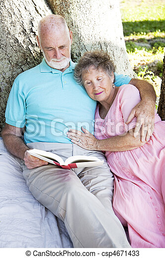 Senior Couple Reading Together Outdoors - csp4671433