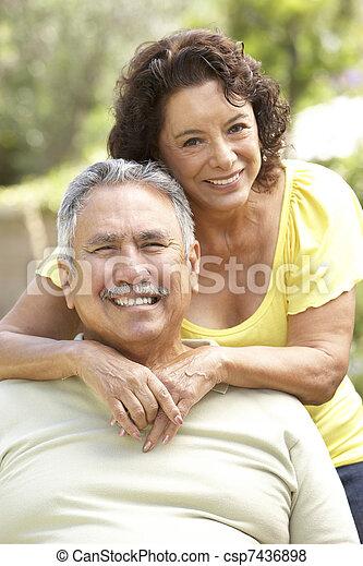 Senior Couple Relaxing In Garden Together - csp7436898