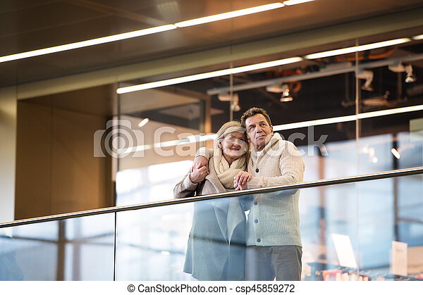 Senior couple standing at the train station, waiting, hugging - csp45859272