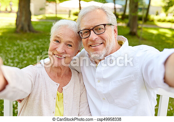 senior couple taking selfie at summer park - csp49958338