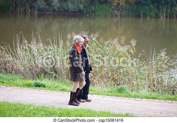 Senior couple walking alongside a lake - csp15061416