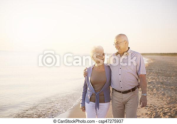 Senior couple walking on the summer beach - csp47275937