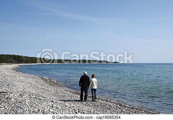 Senior couple walks along coast - csp19565354