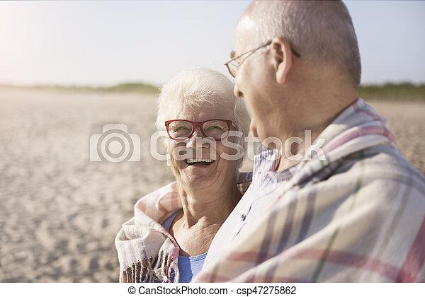 Senior couple warming up under the blanket - csp47275862