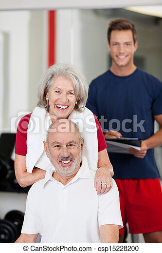 Senior couple with a fitness trainer - csp15228200