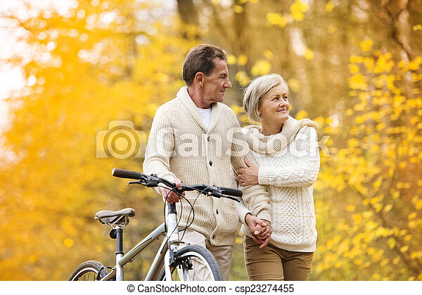 Senior couple with bicycle in autumn park - csp23274455