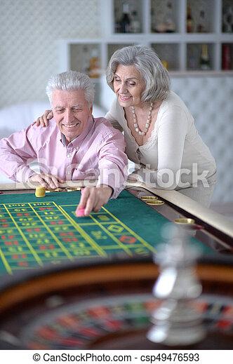 senior couple with casino chips - csp49476593