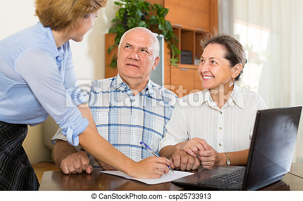 Senior couple with social worker at home - csp25733913
