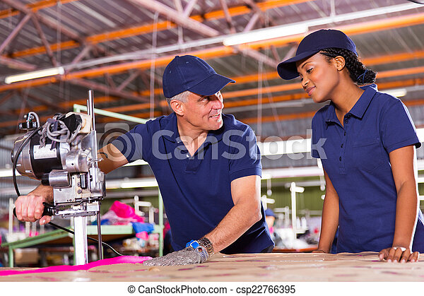 senior cutter teaching young worker cutting fabric - csp22766395