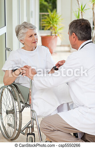 Senior doctor talking with his patient - csp5550266