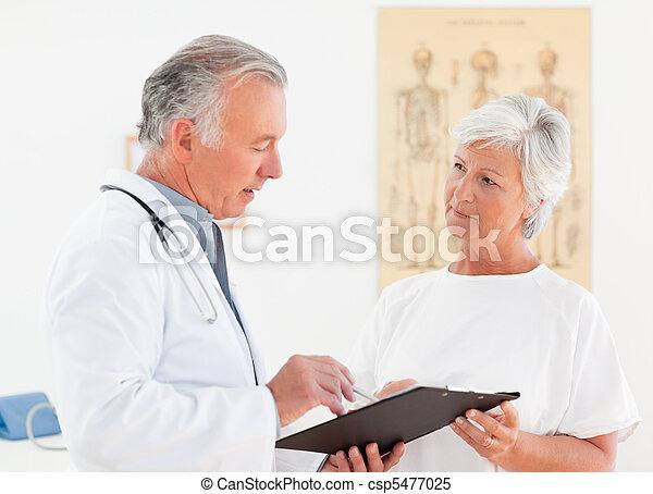 Senior doctor talking with his sick patient - csp5477025