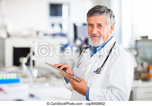 Senior doctor using his tablet computer at work - csp9459942