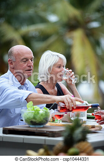 Senior friends having a meal in the garden - csp10444331