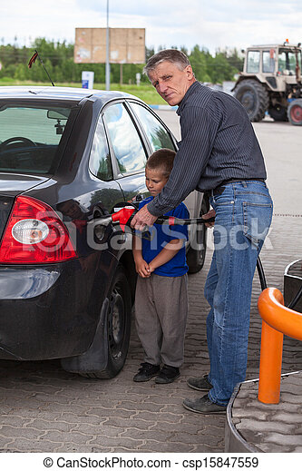 Senior grandfather with young boy refilling car at gas station - csp15847559