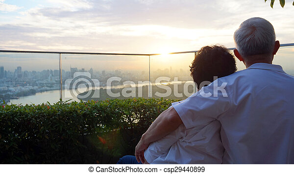 senior looking at sunrise together over city skyline - csp29440899
