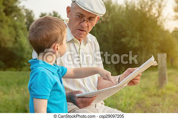 Senior man and child reading a newspaper outdoors - csp29097205