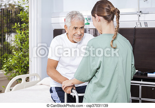 Senior Man Being Assisted By Female Nurse In Using Walker - csp37031139