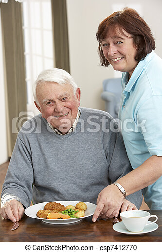 Senior Man Being Served Meal By Carer - csp7412770